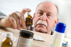 Bouteille de médecine de cueillette d'homme aîné Images stock