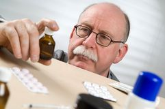 Bouteille de médecine de cueillette d'homme aîné Image libre de droits