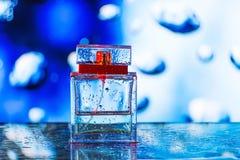 Bouteille de parfum carrée sur le fond bleu, blanc et rouge Images libres de droits