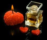 bouteille de parfum, de bougies et de coeurs en gros plan Photographie stock libre de droits