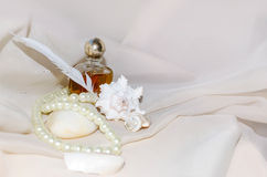 Bouteille de parfum de vintage avec des perles, des mollusques et crustacés, la pierre de mer blanche et la plume Images libres de droits
