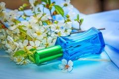 Bouteille de parfum en verre bleue et branche de floraison de cerise Images libres de droits