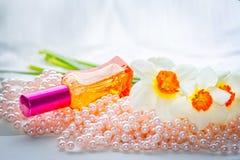 Bouteille de parfum, perles de perle et fleurs en verre rouges de jonquille Photographie stock libre de droits