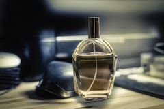Bouteille de parfum placée sur le bureau, fond dans des fournitures de bureau Images libres de droits