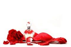 Bouteille de parfum, rose et soutien-gorge rouge Photographie stock