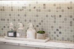 Bouteille de savon liquide avec des accessoires de salle de bains de fond de tuile photographie stock libre de droits