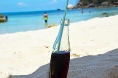 Bouteille de soude brune sur la plage Photographie stock libre de droits