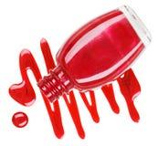 Bouteille de vernis à ongles rouge avec des échantillons de baisse d'émail Photos stock