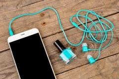 bouteille de vernis à ongles, de téléphone intelligent et d'écouteurs sur la table en bois brune photo stock