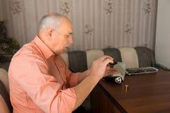 Bouteille de versement de lotion après-rasage de vieil homme en main Photos libres de droits