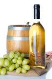 Bouteille de vin avec des raisins blancs et un tonneau sur un sac de toile de jute Photos libres de droits