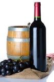 Bouteille de vin avec des raisins noirs et un tonneau sur un sac de toile de jute Photographie stock