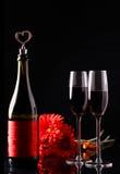 Bouteille de vin avec du liège sous forme de coeur et de deux verres de gerbera de trois rouges Photographie stock