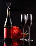 Bouteille de vin avec du liège sous forme de coeur et de deux verres de gerbera de trois rouges Images stock