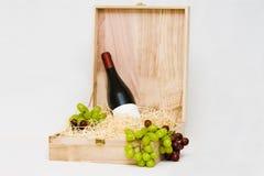 Bouteille de vin dans le cadre en bois avec des raisins Photos libres de droits