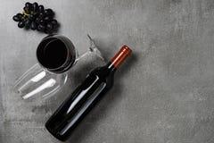 Bouteille de vin, de gobelets et de raisins sur le fond concret Copiez l'espace images stock