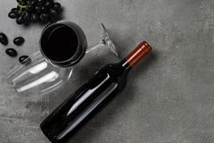 Bouteille de vin, de gobelets et de raisins sur le fond concret Copiez l'espace image libre de droits