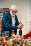 bouteille de vin heureuse d'ouverture d'homme supérieur Photo stock