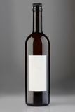 Bouteille de vin rouge avec le chapeau et label vide sur le fond gris Photo libre de droits