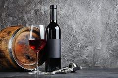 Bouteille de vin rouge avec le verre pour goûter et baril en bois dans la cave foncée photographie stock
