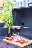 Bouteille de vin rouge, de bifteck et de tomates sur le barbecue dehors Images libres de droits