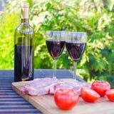 Bouteille de vin rouge, de bifteck et de tomates sur le barbecue dehors Photo libre de droits
