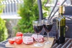 Bouteille de vin rouge, de bifteck et de tomates sur un pique-nique dehors Photographie stock libre de droits