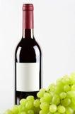 Bouteille de vin rouge et de raisins verts dans l'avant Photos stock