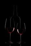 Bouteille de vin rouge et verre de vin sur le fond noir image libre de droits