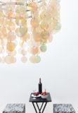 Bouteille de vin rouge sur une table, beau lustre a de décoration Photographie stock