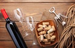 Bouteille de vin rouge, verres de vin, cuvette avec des lièges et tire-bouchon Photographie stock