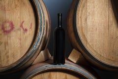 Bouteille de vin sur des barils dans une cave photo stock