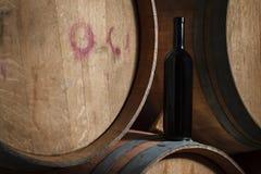 Bouteille de vin sur des barils dans une cave photographie stock