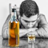 Bouteille de whiskey avec hors de l'homme bu par foyer Photographie stock libre de droits