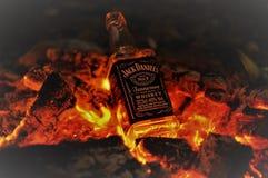 Bouteille de whiskey Jack Daniel sur le feu avec les charbons de bois brûlants pendant la nuit images libres de droits