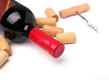 Bouteille du vin rouge, des lièges et du tire-bouchon Photographie stock libre de droits