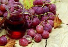 Bouteille en osier et raisins de jus organique de ferme Photographie stock libre de droits