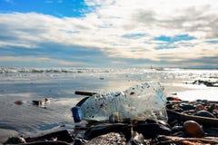 Bouteille en plastique sur le sable humide jeté par la vague de mer image stock