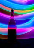 Bouteille en verre avec des étincelles et des vagues de lumière Image stock