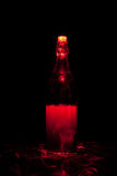Bouteille en verre avec des étincelles et des vagues de lumière Photo stock