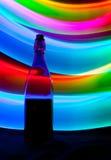 Bouteille en verre avec des étincelles et des vagues de lumière Photographie stock
