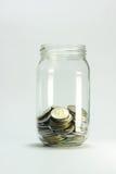 Bouteille en verre avec des pièces de monnaie d'argent Photographie stock libre de droits