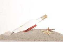 Bouteille en verre avec la note à l'intérieur sur le sable Image stock