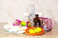 Bouteille en verre avec le mélange pour l'alimentation, les jouets et les couches-culottes de bébé Images stock