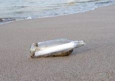 Bouteille en verre avec le message de note sur la plage tropicale Image stock