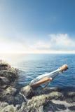 Bouteille en verre avec le message en mer Photographie stock