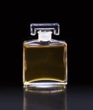 Bouteille de parfum avec le liquide jaune sur le noir Photographie stock libre de droits