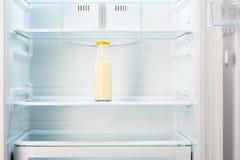 Bouteille en verre de yaourt sur l'étagère du réfrigérateur vide ouvert Image stock