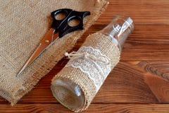 Bouteille en verre diy faite maison Ciseaux, toile de jute, vase fait main sur une table en bois photographie stock