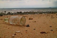 Bouteille en verre sur la plage Photographie stock